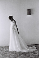 classic grainy black & white photo of bride with strapless wedding gown looking down.