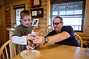 John Daniel Shannon, 48, a former US Army Senior Sniper, is helping his younger son Drake, 11, with his ketchup bottle in their kitchen in Westcliffe, CO, USA, where he retired with his family after a serious brain injury inflicted by an insurgent sniper in Ramadi, Al Anbar Province, Iraq, on November 13th 2004. Daniel fought during the Second Battle of Fallujah and was then moved to nearby Ramadi. Daniel lost his left eye and has multiple health issues because of his injury: memory problems, balance problems, he can't smell and taste well anymore, he suffers from PTSD, has  troubles with large crowds and city surroundings. This is the reason why he and his family moved to a quiet location on the Rocky Mountains. In 2007 Dan helped the Washington Post to uncover patients' neglect at the Walter Reed Army Medical Center; he also testified before Congress. Torrey, 42, his wife, is a freelance writer and a contributor for the Huffington Post; she's also campaigning to improve the situation of veterans' families.