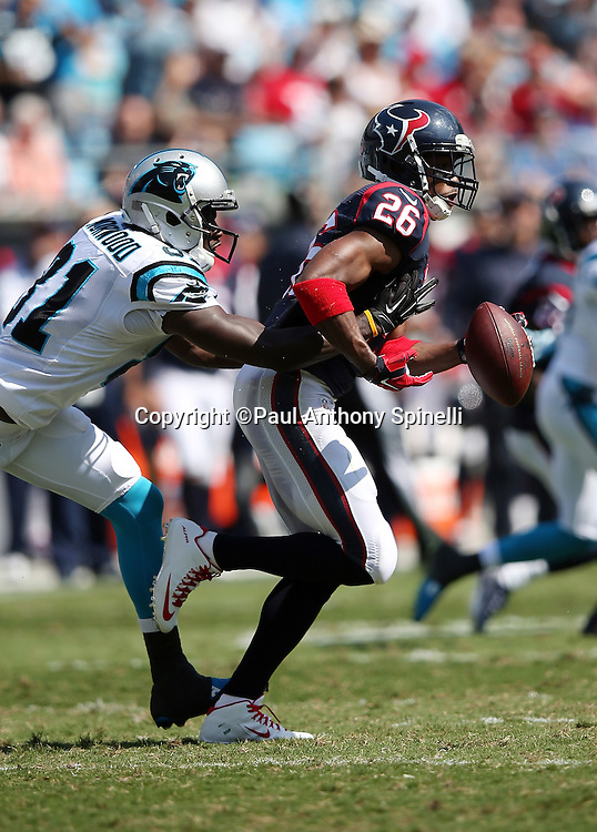 Houston Texans free safety Rahim Moore (26) loses the ball on a strip by Carolina Panthers wide receiver Kevin Norwood (81) after intercepting a second quarter pass in the end zone during the 2015 NFL week 2 regular season football game against the Carolina Panthers on Sunday, Sept. 20, 2015 in Charlotte, N.C. The Panthers won the game 24-17. (©Paul Anthony Spinelli)