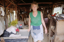 Woman standing in kitchen attached to house on farm near Banes; Cuba,
