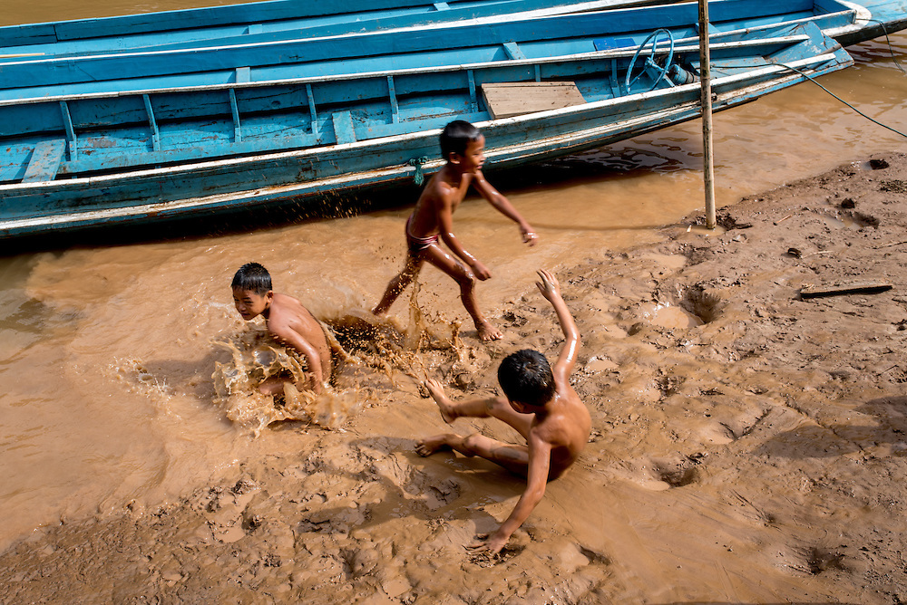Children play on the river banks in the village of Khoc Kham. The village is not connected to the main electrical grid and many residents operate their own turbines to power lights and sometimes small appliances.