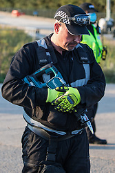 West Hyde, UK. 14th September, 2020. An officer from a Hertfordshire Police cutting team prepares to remove HS2 Rebellion activists using lock-on arm tubes to block a gate to the South Portal site for the HS2 high-speed rail link. Anti-HS2 activists blocked two gates to the same works site for the controversial £106bn rail link, one remaining closed for over six hours and another for over twelve hours.