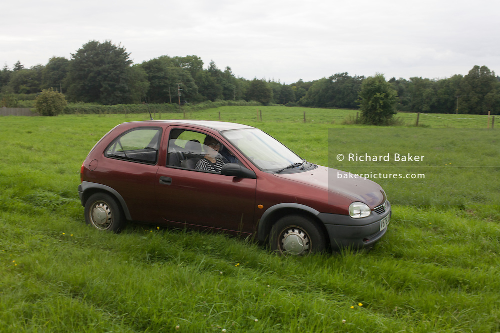 A 17 year-old teenage girl takes her first driving lesson in a meadow on private land.