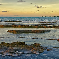 Go slow bend rocky shores on a low tide day duting sunset. Tops of the rocks are exposed leaving shallow ponds of water inbetween.