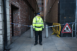 © Licensed to London News Pictures . 29/12/2013 . Manchester , UK . A PCSO in front of police tape on Whitworth Street West parallel to the River Medlock in Manchester City Centre . The search for 17 year old Adam Pickup from Stockport , who was last seen in the early hours of Saturday 28th December in Manchester City Centre following a night out with friends as , this evening (Sunday 29th December 2013), Greater Manchester Police say they have arrested two men in connection with the teenager's disappearance . Photo credit : Joel Goodman/LNP
