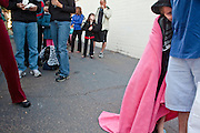 """Oct. 24, 2009 - SCOTTSDALE, AZ: A child wrapped in a blanket hugs his father's leg while waiting to get an H1N1 vaccination at Scottsdale Healthcare's Community Health Services clinic Saturday morning. The first publicly administered H1N1 (""""swine flu"""") vaccinations were given in the Phoenix area Saturday. About 52,000 doses of the vaccine, in both injection and nasal spray form, were available on a first come first served basis, but only to those in so called """"high risk"""" groups: pregnant women, children 6 months to 4 years old, children 5 years to 18 years with underlying health concerns and direct caregivers of infants less than 6 months old. More than 700 people lined up at Scottsdale Health Care, which had 500 doses of the vaccine to administer.     Photo by Jack Kurtz"""