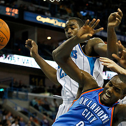 January 11, 2012; New Orleans, LA, USA; Oklahoma City Thunder power forward Serge Ibaka (9) has the ball knocked away by New Orleans Hornets center Chris Kaman (35) and forward DaJuan Summers (22) during the third quarter of a game at the New Orleans Arena.   Mandatory Credit: Derick E. Hingle-USA TODAY SPORTS