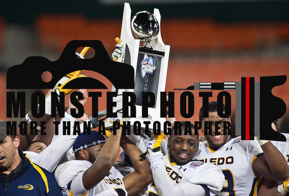 Toledo players celebrate on stage with the 2011 Military Bowl trophy after defeating Air Force 42-41 Wednesday, Dec. 28, 2011 at RFK Stadium in Washington DC..