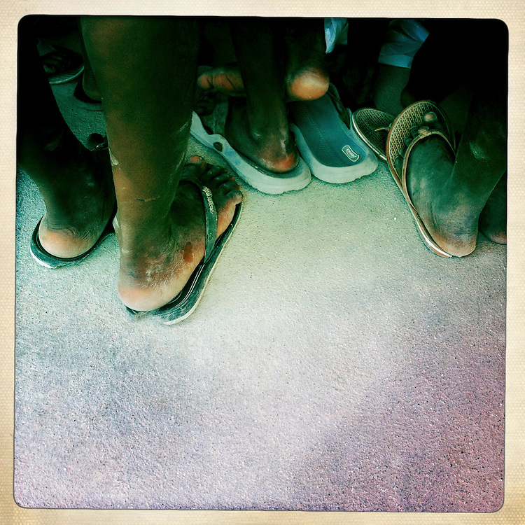 The feet of children gathered together at the Corail camp on Wednesday, April 4, 2012 in Port-au-Prince, Haiti.