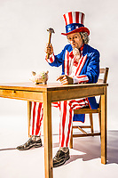 Uncle Sam seated at a table holding a hammer above a piggy bank as if about to bust it open. A conceptual shot for the US Treasury, tax revenues, breaking the bank, federal deficits.