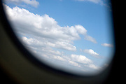 airplane window while making a turn with clouds and sky
