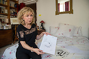 March 6, 2015, Paris, France. Writer Maryse Wolinski (1943, Algiers), sitting on her bed in the bedroom of her Paris apartment, shows a drawing from 1971 made by her husband Georges Wolinski (1934-2015), a French artist who often portrayed her. After the Islamist terrorist attack on Charlie Hebdo and his death,  two month earlier, Maryse Wolinski deals with loss. The cartoonist Georges Wolinski was 80 years old when he was murdered by 2 jihadists, he was one of the 12 victims of the massacre in the Charlie Hebdo offices on January 7, 2015 in Paris, after publishing caricatures of Mohammed, considered blasphemous by some Muslims. Georges Wolinski defended freedom, secularism and humour and was one of the major political cartoonists in France. The couple was married and lived since 47 years together. Photo: Steven Wassenaar.