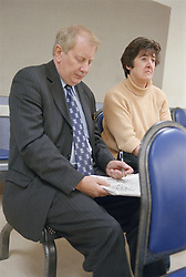 Man with suspected broken ankle or foot doing newspaper crossword while waiting with wife in Accident and Emergency department of hospital,
