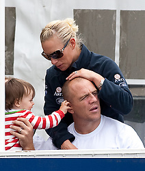 GATCOMBE, ENGLAND- AUG 7: Zara and Mike Tindall watch a display in the main arena at the British Festival of Eventing at Gatcombe Park in Gloucestershire. <br /> The child of James Simpson Daniel (Gloucester Rugby and Usher at wedding) plays with Mike.