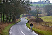 Man on a bicycle  in a country lane, Oxfordshire, United Kingdom