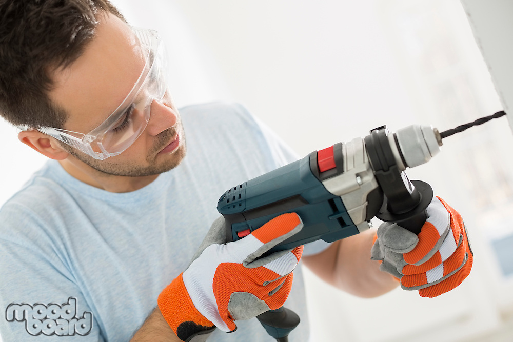 Mid-adult man drilling in wall