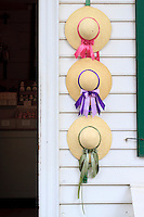 3 women's hats hung on a wall next to the door.