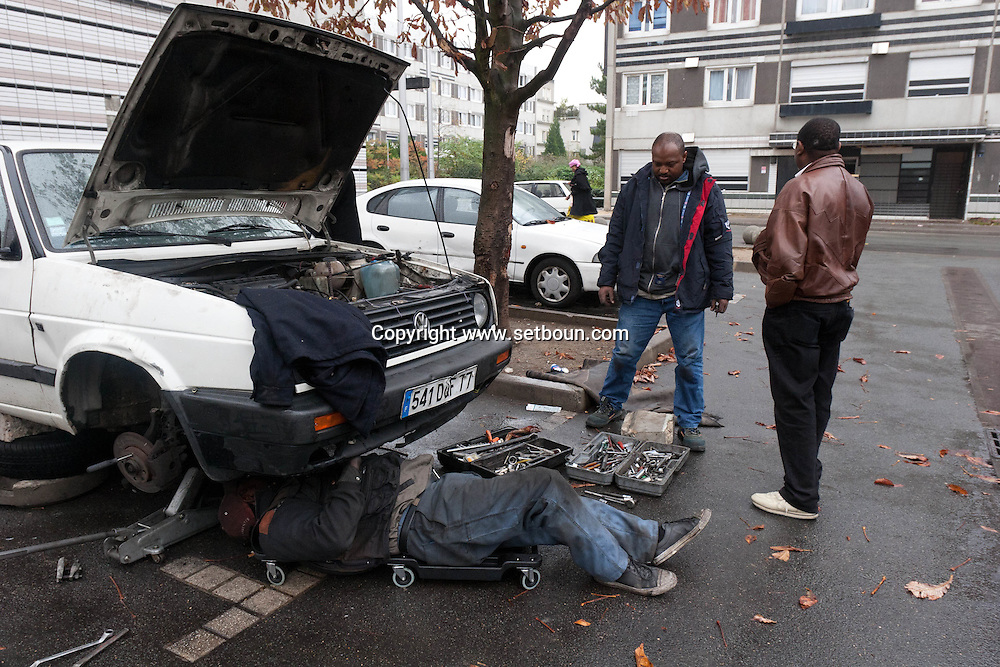 = La Courneuve , cite of 4000.  Oudo is repairing cars in the cite, it s the underground economy  Paris  France    /// La Courneuve, cite des 4000 , Oudo, le garagiste independant est camerounais et repare les voitures sur place,  Paris  France +