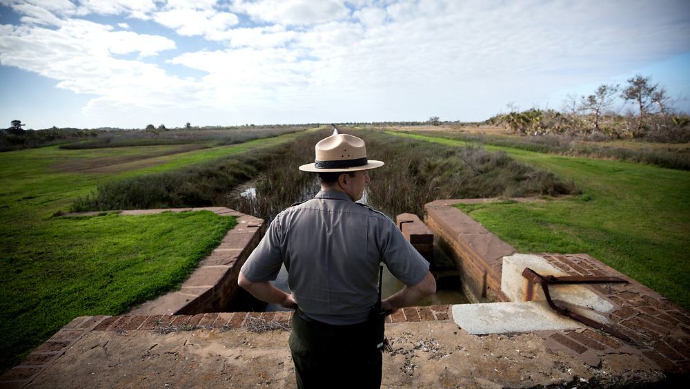 COCKSPUR ISLAND, GA. - FEBRUARY 21, 2018: Surrounded by marshes and a levee system, Fort Pulaski National Monument ranger Joel Cadoff surveys a canal used to fill and drain the moats surrounding the fort. (WABE Photo/Stephen B. Morton)