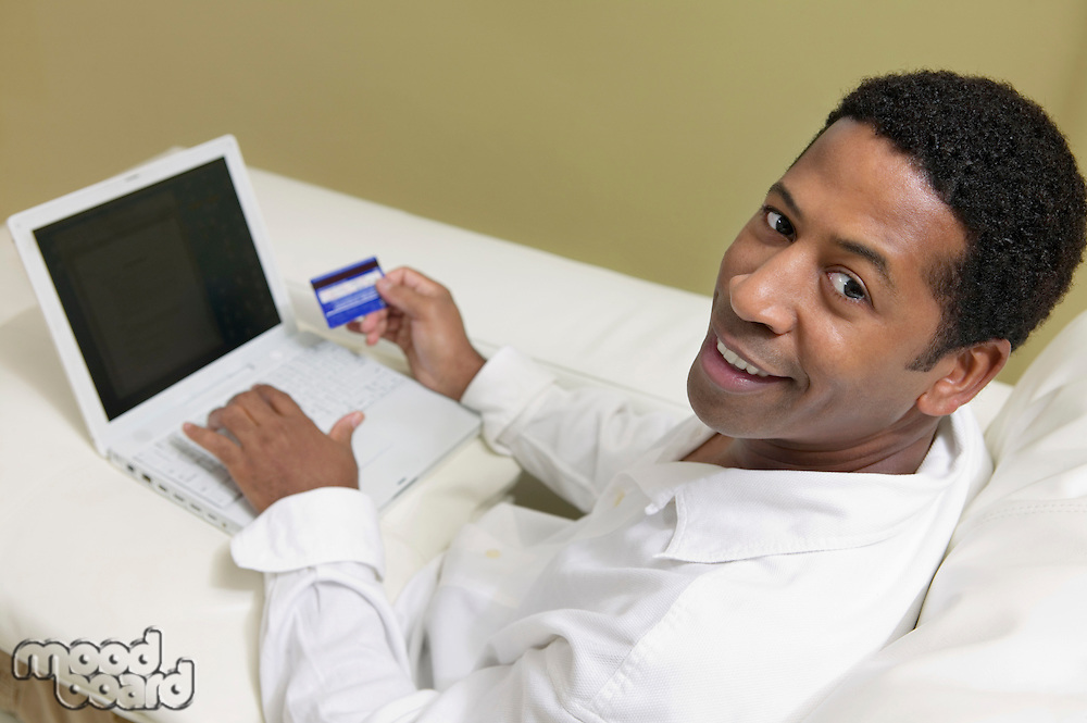 Man Using Credit Card to Make Purchase with Laptop