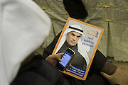 A Kuwaiti man reads messages on his mobile phone during a Jan. 18 rally to mark the inauguration of the elections HQ of veteran Kuwaiti politician and three-time former Speaker of Parliament Ahmad Al-Sadoun in Kuwait City.  Al-Sadoun is among some 340 candidates who are running in the Feb. 2, 2012 polls to elect a new 50-seat National Assembly (parliament).