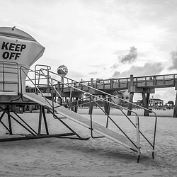 Pensacola Beach lifeguard tower five and Gulf Pier sunrise black and white panorama photo on Casino Beach. Pensacola Beach Florida is a coastal city on Santa Rosa Island in the Emerald Coast of the Southeastern United States of America. Panoramic photo ratio is 1:3. Copyright ⓒ 2018 Paul Velgos with All Rights Reserved.