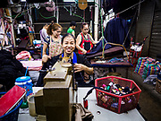 23 FEBRUARY 2018 - BANGKOK, THAILAND: A seamstress sews clothes in one of the few shops still open in Pratunam Market. Pratunam Market was one of the largest clothing markets in Bangkok. New airconditioned markets, like Platinum and Palladium malls opened nearby, siphoning away customers. Now there are only a handful of merchants left in the market and Bangkok city officials have plans to shut the market and redevelop the land.      PHOTO BY JACK KURTZ
