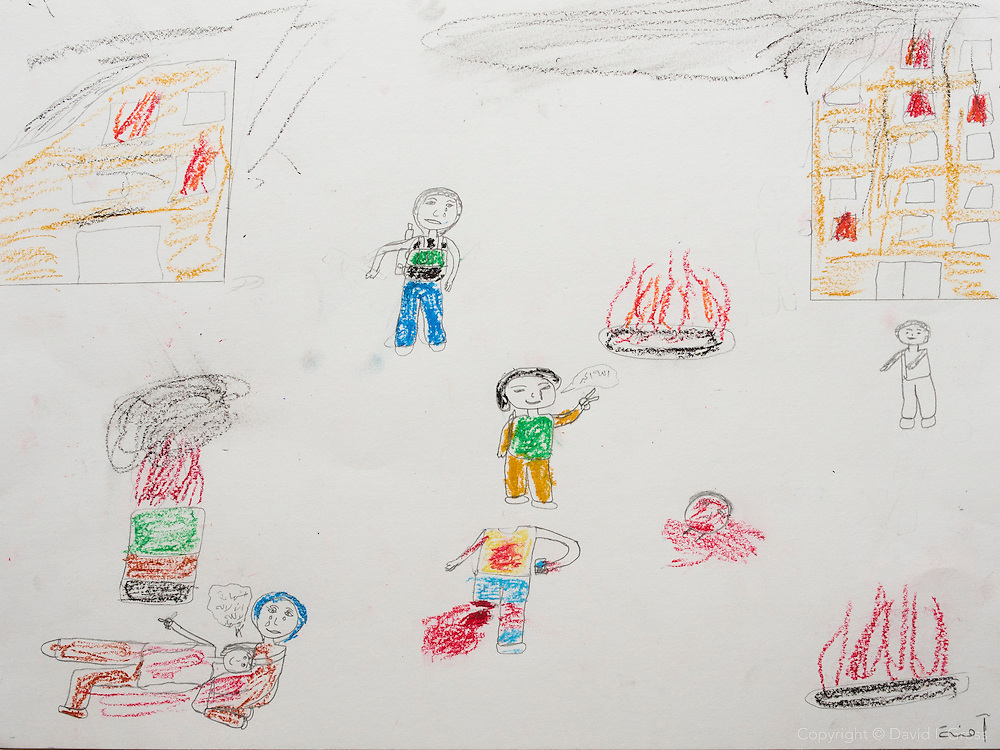 """There is a hospital in the upper right, a mother crying for her son in the lower left. The child in the bottom center was eating a candy bar when a bomb blew his head off. The girl who drew this witnessed it. He remained standing for a few moments with the candy bar after it happened."" Drawing by Syrian girl, age 13. (Topic for this session: dealing with loss.)"