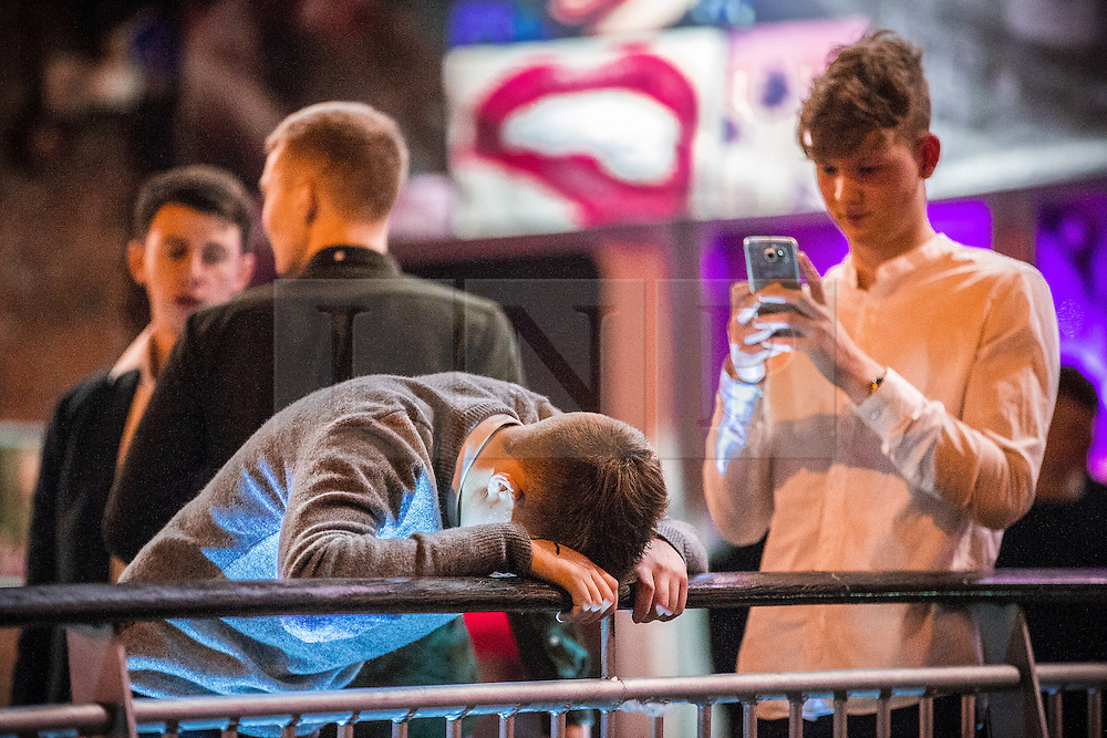 "© Licensed to London News Pictures . 19/12/2015 . Manchester , UK . A man takes a photograph of another slouched over barriers at Deansgate Locks . Revellers in Manchester enjoy "" Mad Friday "" - also known as "" Black Eye Friday "" - the day on which emergency services in Britain are typically at their busiest , as people head out for parties and drinks to celebrate Christmas . Photo credit : Joel Goodman/LNP"