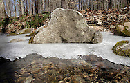 Mamakating, New York - A stream flows under ice crystals and past a large rock on a cold spring day at the Bashakill Wildlife Management Area on March 26, 2011.