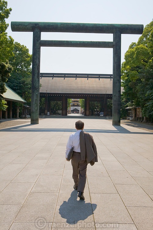 A man walks towards the entrance to the Yasukuni Jinja Shinto Shrine in Chiyoda, Tokyo, Japan. The shrine was built in 1869 to honor those who lost their lives serving Japan.