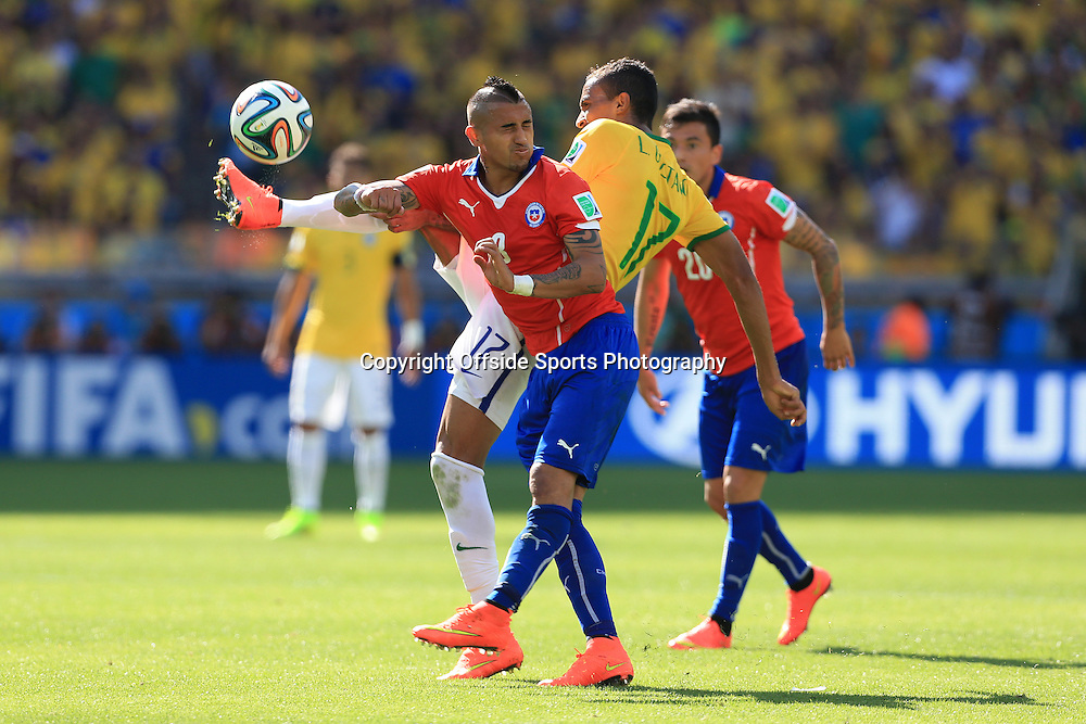 28th June 2014 - FIFA World Cup - Round of 16 - Brazil v Chile - Luiz Gustavo of Brazil battles with Arturo Vidal of Chile - Photo: Simon Stacpoole / Offside.