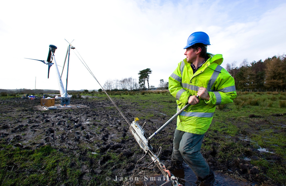 Worker winching up a small domestic 6 KW wind turbine
