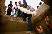 After dancing with the dead at a reburial ceremony in Belaveno, Bezanozano Ethnic Area, Madagascar, the bodies are returned to the family tomb which is then sealed until the next burial or reburial. The famadihana, the Madagascan reburial ceremony, is a custom in the highlands of Madagascar. The purpose of the ritual is to induce the ancestors to impart their blessings to their descendants, without which they cannot have a good life. The famadihana is held during the cooler half of the year, when the dead are said to be freezing in their graves and therefore need new clothing.