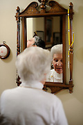 Elderly woman putting on the final touches dressing.