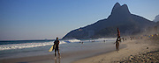 A man carrying a surf board on the beach, Rio de Janeiro, Brazil.