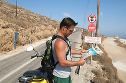 good looking tourist stopping to read a map while standing next to a moped in Greece