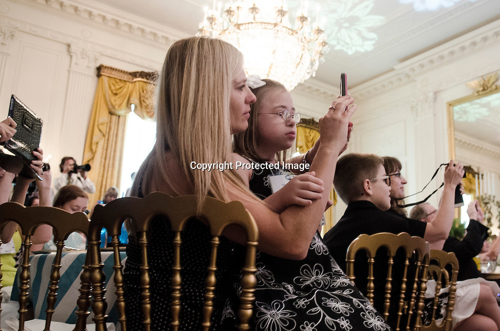 "First Lady Michelle Obama speak as Makenna Hurd(9) with mom Amanda Hurd of Mascot, TN listen during the Kids' ""State Dinner"" at the White House which was hosted by First Lady Michelle Obama in the East Room on July 9, 2013. Makenna was one of 54 winners from across the country with her ""Makenna's Bodacious Banana Muffins"" as part of the Healthy Lunchtime Challenge. Photo by Kris Connor"