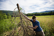 Mark Hornyak works to clean underbrush and debris from the shooting sports field during Staff Week. Because the camp grounds are only used for a couple of months out of the year nature can really start to reclaim some areas. Most of the staff arrive a week before the campers to train up and make everything ready.