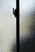 silhouette of person behind reinforced safety glass