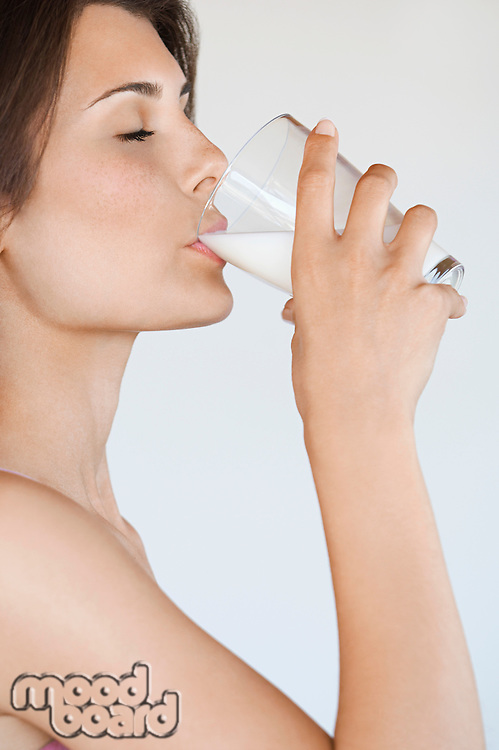 Young woman drinking milk side view