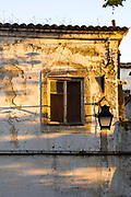 Light and shade on old derelict white and yellow house in need of renovation work in Evora, Portugal