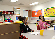 Zaria Larsen (from left), 3, of Cedar Rapids glances at Taylor Robinson, 3, of Atkins as they each their afternoon snack at Building Blocks Child Care in Cedar Rapids on Wednesday February 25, 2009.  (Stephen Mally/Freelance)