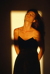 woman in dress with a falling strap leaning against the wall in afternoon light