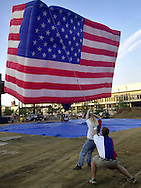 PHILADELPHIA - JULY 3:  Grounds crew members Teri Dillibero (L), and Cameron Wise (R), struggle to control the American Flag hot air balloon, at the commemoration to the one year countdown of the grand opening of the National Constitution Center, July 3, 2002, in Philadelphia.  The American Flag shaped hot air balloon , which is 53 feet tall and weighs 1500 pounds, will travel across the country with the official NCC flag, and return to the National Constitution Center on Flag Day 2003. The National Constitution Center is scheduled to open July 4, 2002.  (Photo by William Thomas Cain/Getty Images)