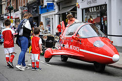 © Licensed to London News Pictures. 17/06/2018. LONDON, UK. A woman and children view a Pulse 'Jet Fighter' Autocycle finished in Red Arrows Red, complet with RAF Roundels ,at the 6th Annual Classic and Supercar Pageant held at St John's Wood High Street.  Traditionally taking place on Fathers' Day, the show brings together an eclectic mix of exotic and popular vehicles attracting visitors young and old and raises funds for the local charity, The St John's Hospice.  Photo credit: Stephen Chung/LNP