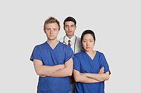 Portrait of confident healthcare workers standing over gray background