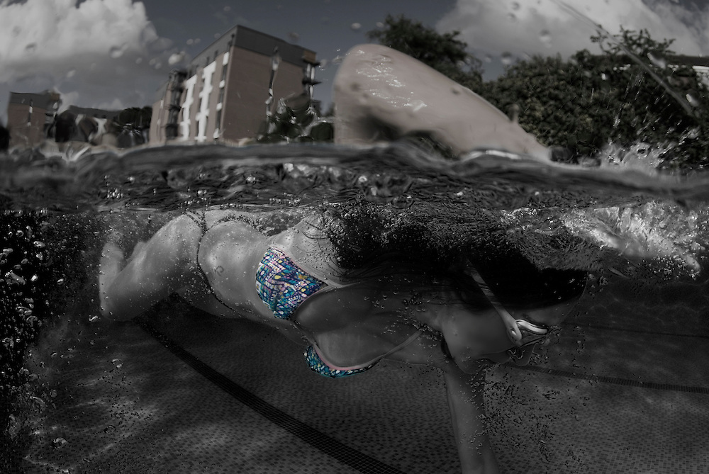 Over under shot of a girl in a blue patterned bikini swimming front crawl in an outdoor pool.  The shot is half above and half below the waterline and uses a combination of monochrome, reduced colour saturation and selective colour.