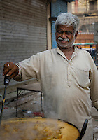 NEW DELHI, INDIA - CIRCA OCTOBER 2016: Food stall merchant around the spice market and the Chandni Chowk area in Old Delhi.