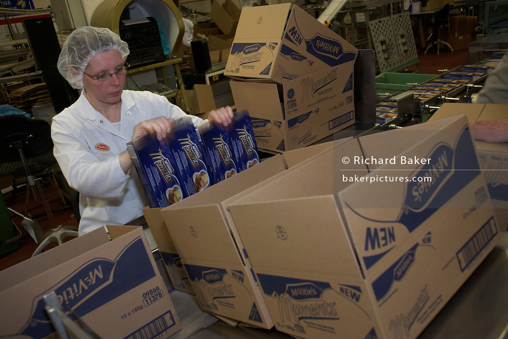 Female employee boxes finished Moments biscuitsof at the United Biscuits-owned Delacre production factory in Lambermont